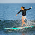 A Woman Rides A Wave On A Longboard by Ty Milford