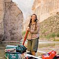A Woman Unloads Gear From Her Canoe by David Nevala
