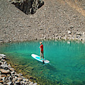 A Young Male Paddleboarding On A Small by Brandon Huttenlocher