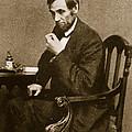 Abraham Lincoln Sitting At Desk by Mathew Brady