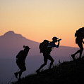 Adventure Racing Team Hiking At Sunset by Corey Rich