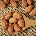 Almonds On A Spoon With Brown Background by Brandon Bourdages