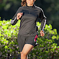 An Athletic Woman Trail Running by Corey Rich