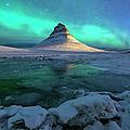 Aurora Over Kirkjufell Mountain Iceland by Ratnakorn Piyasirisorost
