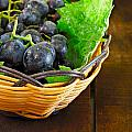 Basket Of Grapes On Rustic Wooden Table by Ken Biggs
