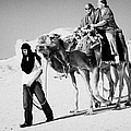 bedouin guide in modern clothing leads british tourists riding camels and wearing desert clothes into the sahara desert at Douz Tunisia by Joe Fox