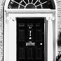 Black Georgian Door With Brass Letterbox Door Knob And Knocker And Fanlight In Dublin by Joe Fox