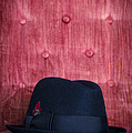 Black Hat On Red Velvet Chair by Edward Fielding