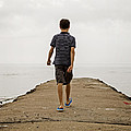 Boy Walking On Concrete Beach Pier by Edward Fielding