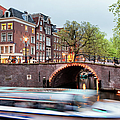 Canal Bridge And Boat Tour In Amsterdam At Evening by Artur Bogacki