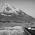 cars in the evening on the road towards Errigal mountain donegals highest peak against a blue sky between dunlewey and gweedore white quartzite conical cone county Donegal Republic of Ireland by Joe Fox