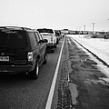 cars waiting on train crossing trans-canada highway in winter outside Yorkton Saskatchewan Canada by Joe Fox