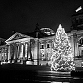 christmas tree and german flag flying fluttering on flagpole outside reichstag building Berlin Germany by Joe Fox