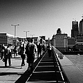 commuters and city workers cross london bridge over the river thames in the morning central London England UK by Joe Fox
