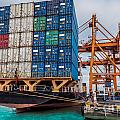 Container Cargo Freight Ship With Working Crane Loading by Anek Suwannaphoom