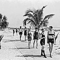 Couples Strolling Along The Pathway On The Beach. by -