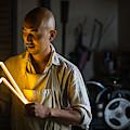 Craftsmen Holding A Lightning Bolt Shaped Neon Light by Trevor Williams