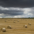 Dark Storm Clouds Over A Field With Hay by John Short
