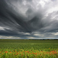 Dark Storm Clouds Over A Field With Red by John Short