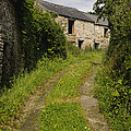 Dirt Path To Stone Building by John Shaw