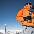 Dressed In Orange, A Skier Sips A Warm by Michael Hanson