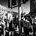 early morning commuters waiting to cross the road pedestrian crossing London England UK by Joe Fox