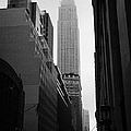 empire state building shrouded in mist in amongst dark cold buildings on 33rd Street new york city by Joe Fox