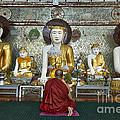 faithful Buddhist monk praying at Buddha Statues in SHWEDAGON PAGODA by Juergen Ritterbach