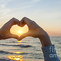 Fingers Heart Framing Ocean Sunset by Elena Elisseeva