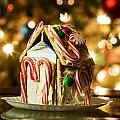 Gingerbread House Against A Background Of Christmas Tree Lights by Alex Grichenko