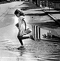 Girl Playing In A Puddle by Retro Images Archive