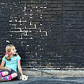Girl Sitting On Ground Next To Brick Wall by Jennifer Huls