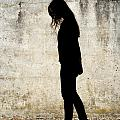 Girl Walking In Front Of Cement Wall by Jim Corwin