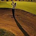 Golfer Taking A Swing From A Golf Bunker by Darren Greenwood