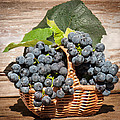 Grapes And Leaves In Basket by Len Romanick