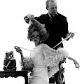 Hairstylist Kenneth Holding The Hair Of A Model by Bert Stern