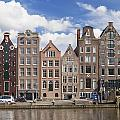 Historic Buildings Along The Damrak Canal In Amsterdam by Roberto Morgenthaler
