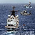 Hms Cornwall Is Pictured Receiving Stores By Merlin Helicopter  by Paul Fearn