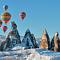 Hot Air Balloons Over Snow Covered Rock by Izzet Keribar