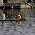 Ladies Plying A Small Boat In The Dal Lake In Srinagar - In Fron by Ashish Agarwal