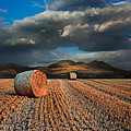 Landscape Of Hay Bales In Front Of Mountain Range With Dramatic  by Matthew Gibson