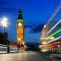 London Uk Red Bus In Motion And Big Ben At Night by Michal Bednarek