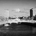 Looking Down The Liffey Towards The Hapenny Ha Penny Bridge Over The River Liffey In Dublin by Joe Fox