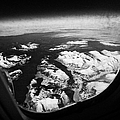 Looking Out Of Aircraft Window Over Snow Covered Fjords And Coastline Of Norway  by Joe Fox