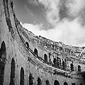 Looking Up At Blue Cloudy Sky And Upper Tiers Of The Old Roman Colloseum At El Jem Tunisia by Joe Fox