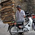 Man Carrying Cardboard On The Back Of His Scooter by Sami Sarkis