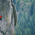 Man Climbing On A Big Granite Spire by Corey Rich