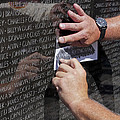 Man Getting A Rubbing Of Fallen Soldier's Name At The Vietnam War Memorial by B Christopher