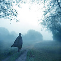 Man In Top Hat And Cape On Foggy Dirt Road by Jill Battaglia
