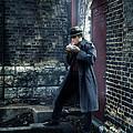 Man In Trenchcoat Lighting A Cigarette by Jill Battaglia